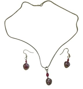 Goldtone ruby with flowers motif inside clear beads.